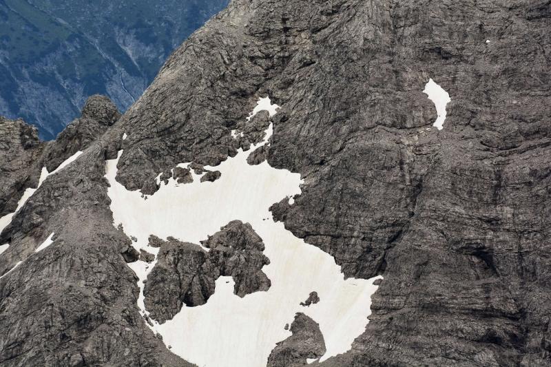 Schneereste bedecken einen felsigen Hang.