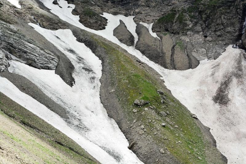 Eine geschwungene Geröllrippe mit Grün und Stein zwischen den Schneeresten vom vergangenen Winter.